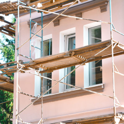 Painting and Plastering Exterior House Scaffolding Wall. Home Facade Insulation, Sctucco and Painting Works During Exterior Wall  Renovations and Repair.